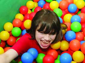 Young man with a disability playing in a ball pool.