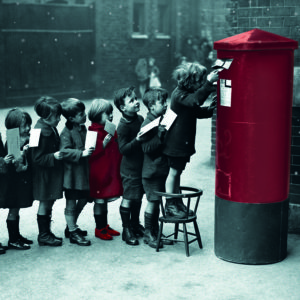 1926, England, UK --- Children from the Red Lion Street School line up to mail letters on a street in England. --- Image by © Hulton-Deutsch Collection/CORBIS