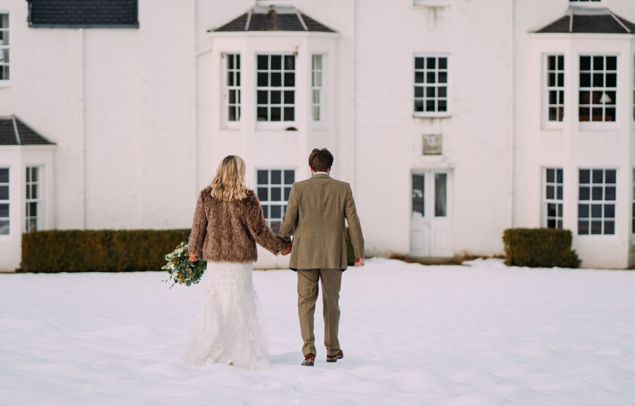 bride and groom walking towards Kindrochet lodge on Atholl Estate