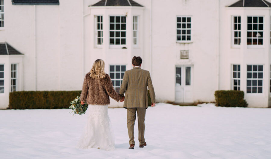 couple walking in snow at wedding