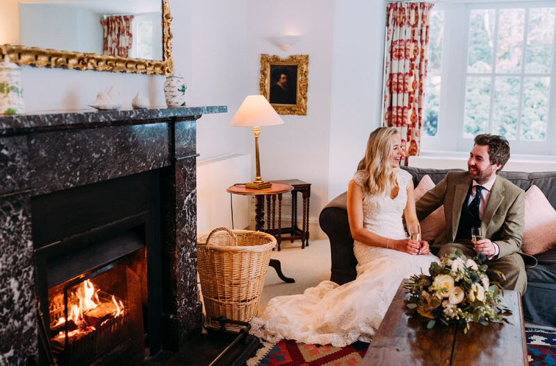 wedding couple drinking champagne by open fire