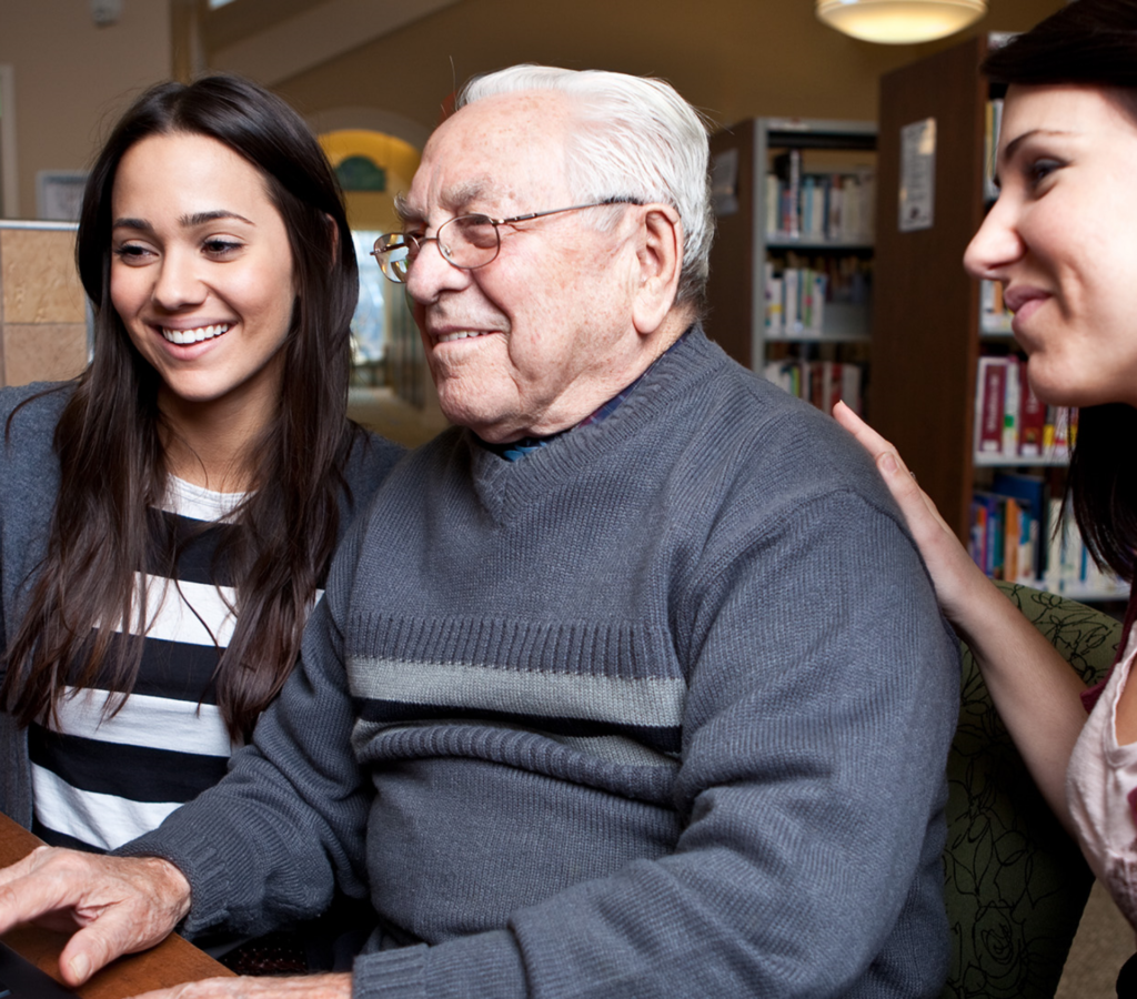 Two younger girls assisting an older gentleman in a library. All three are smiling.