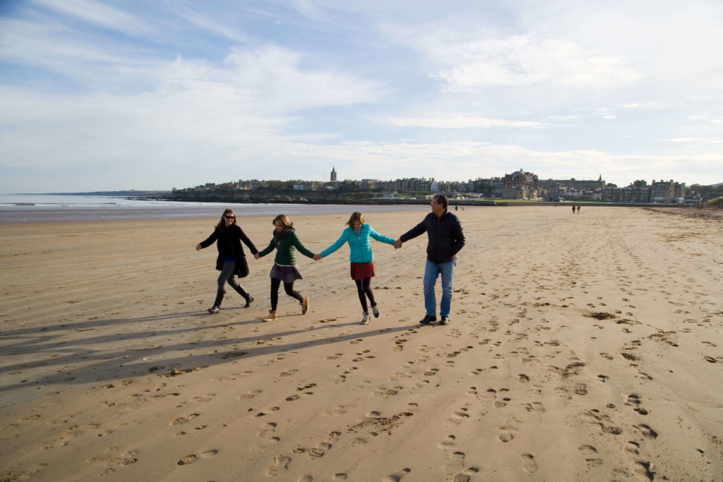 Family walking through West St Andrews Sands