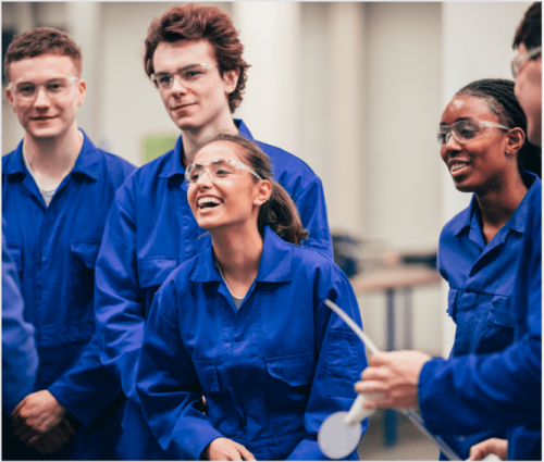 Group of people wearing safety glasses and blue boiler suits