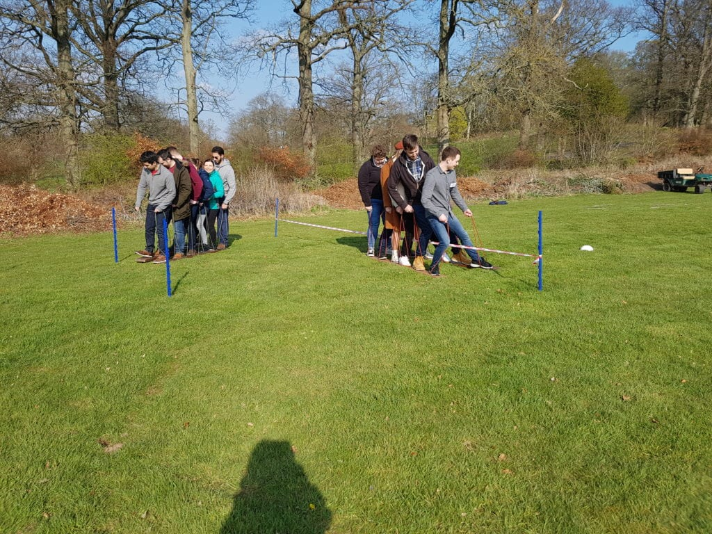 Outdoor challenge showing students traversing ground as a group on two planks of wood