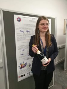 Marie holding her prize bottle in front of her poster.
