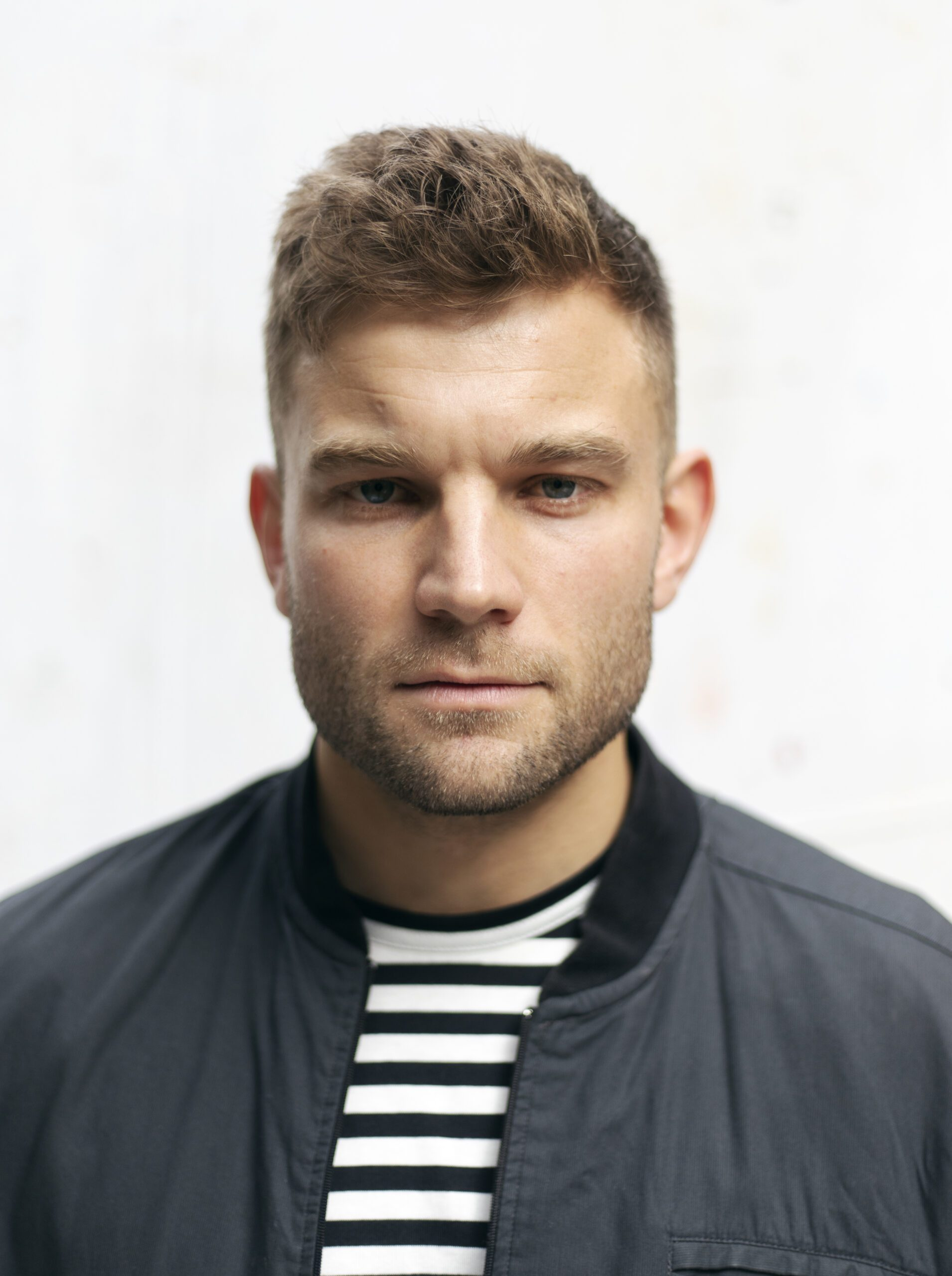 Head shot of Alex Cooper wearing a stripped shirt and navy jacket