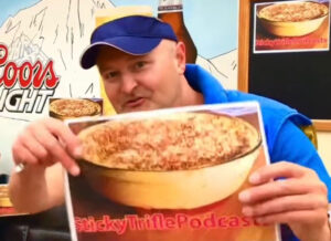 Errol, who wears a blue cap, is holding up a picture of a trifle with text on it which reads Sticky Trifle Podcast