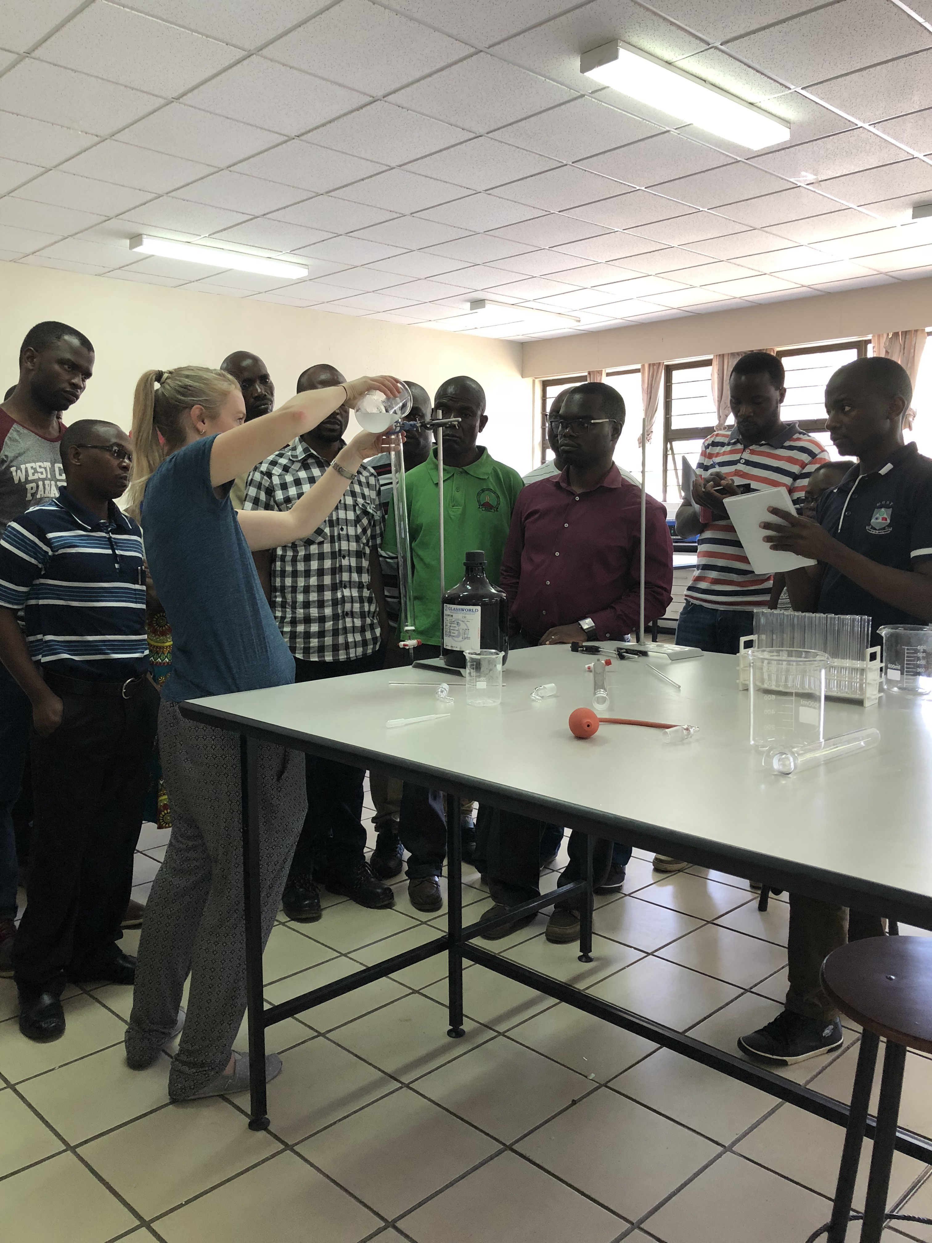 Lauren shows the students how to prepare a column to purify products from a chemistry reaction