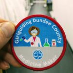 Medicine maker girlguiding badge in front of drug discovery unit lab