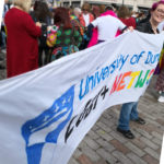 Image shows Erin Hardee holding the University of Dundee LGBT+ Network banner at Dundee Pride 2018