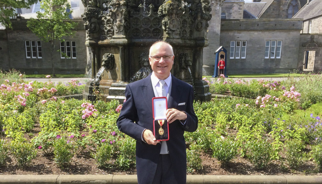Professor Sir Mike Fergusons stands in fromt of a fountain and flowerbeds at Holyrood Palace. He holds the medal indicating his knighhood