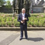Prof Sir Mike Ferguson in the grounds of Holyrood Palace holding his knighthood medal.