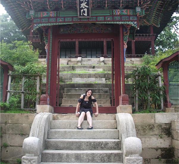 Joana Faria sits on steps in a garden in Seoul, South Korea