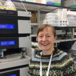 Susan Wyllie stands in front of lab equipment